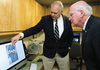 Imagen: El profesor de investigación musculo-esquelética de la Universidad de Vermont, Bruce Beynnon, PhD, a la izquierda, describe como la Universidad de Vermont usa su máquina de investigación de RM para la investigación de las lesiones de rodilla, al Senador de los EE.UU, Patrick Leahy (Fotografía cortesía de COM Design & Photography).